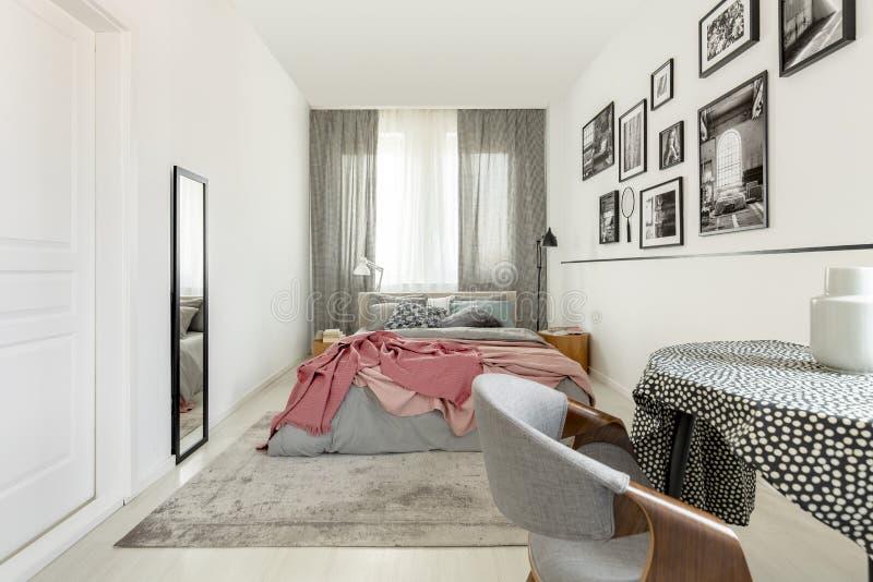 De lijst met doted tafelkleed in helder slaapkamerbinnenland met wit leeg muur, spiegel en koningsgroottebed met grijs beddegoed  stock fotografie