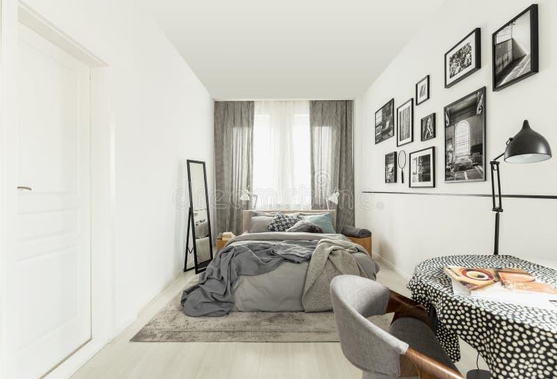 De lijst met doted tafelkleed in helder slaapkamerbinnenland met witte muur stock fotografie