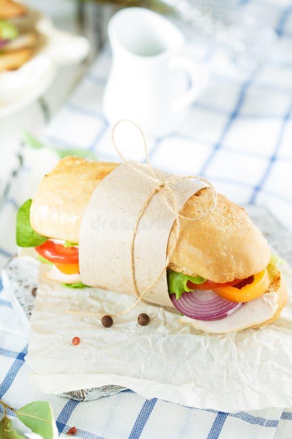 De lijst van Dinning Smakelijke sandwich van knapperig brood met kip, tomaten, ui, sla, kaas en kruiden op lichte houten bedelaar royalty-vrije stock fotografie
