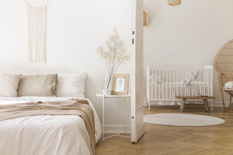 De lijst van het witmetaalbed met decor en koffiemok door het bed in helder slaapkamerbinnenland met deur aan pasgeboren babyruim stock foto