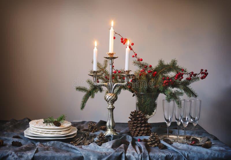 De lijst van Kerstmis het plaatsen De glazen en de kaarsen van Champagne op de lijst stock afbeelding
