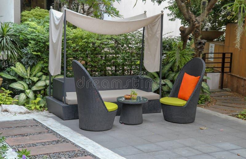 De lijst van de rotantuin en stoelen, het Dineren tuinstoel openlucht in tuin royalty-vrije stock afbeelding