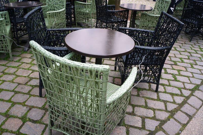 De lijsten van de koffiecirkel en rieten stoelen op straatbestrating stock afbeeldingen