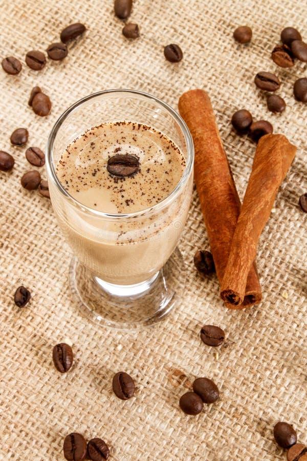 De likeur van de koffieroom in een glas met koffiebonen en kaneel stock fotografie