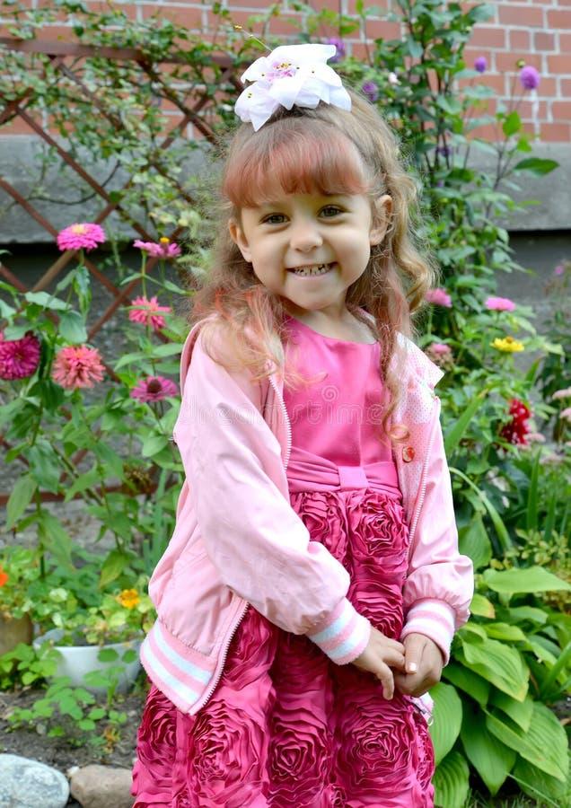 De lilla gladlynta flickakostnaderna i en trädgård mot bakgrunden av blommor royaltyfri bild