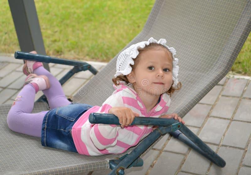De lilla lyckliga flickalögnerna i en chaise är slö arkivbild
