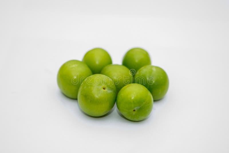 De lilla turkiska gröna plommonerna på den vita bakgrunden arkivfoton