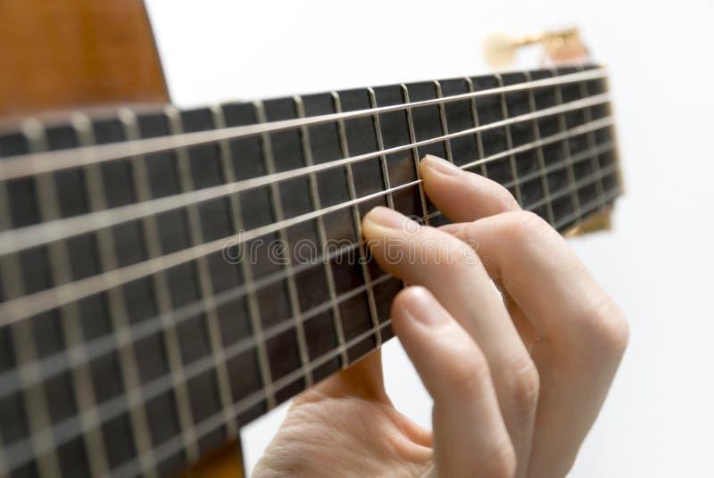 De linkerhand van de speler van de gitaar stock foto's