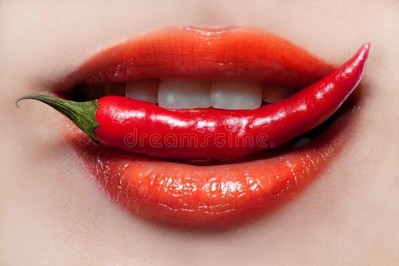 De lippen van de vrouw en Spaanse peperpeper stock foto's