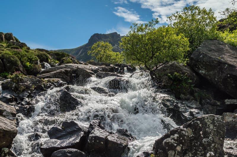 De Llyn idwal una cascada corre abajo de la ladera en Cwm Idwal imagen de archivo libre de regalías