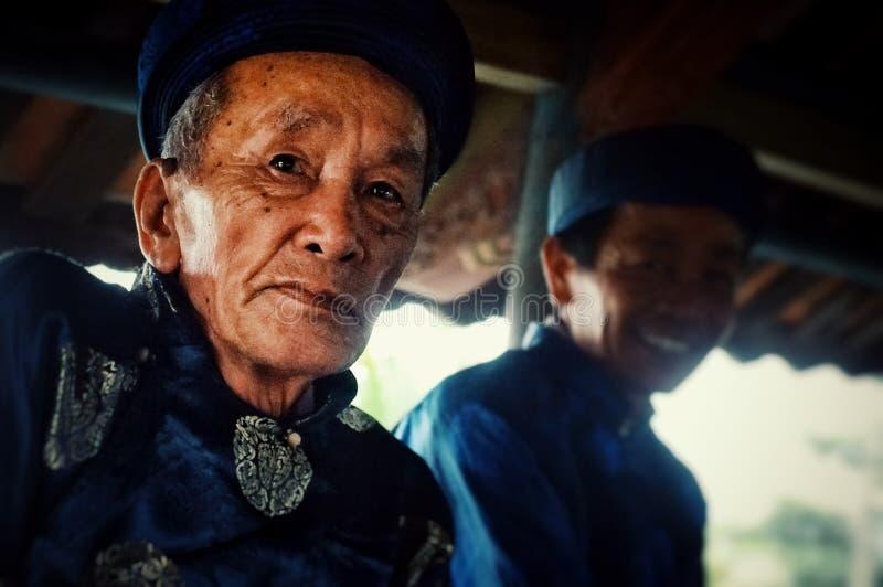 de lokale godsdienstige leiders zegenen een brug en tonen één of ander voedseloffer in traditionele kleding met kaarsen stock foto's