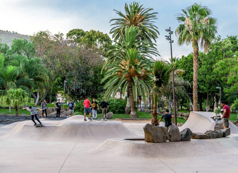 De lokale jonge geitjes genieten van berijdend skateboards en autopedden in een vleetpark in het Park van La Granja in Santa Cruz royalty-vrije stock afbeelding