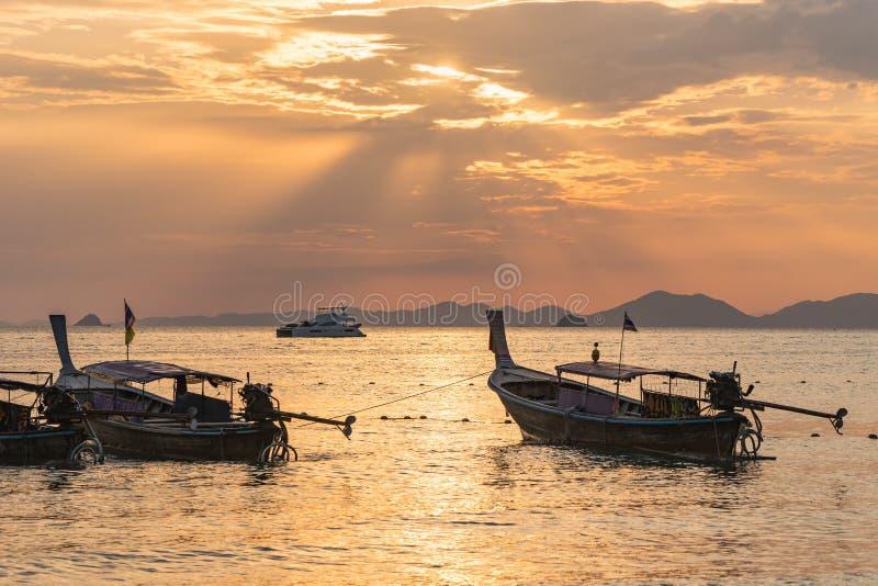 De lokale Thaise boten van de longtailmotor onder gouden zonstralen in het zeewater bij oranje zonsondergang in Ao Nang in Krabi stock afbeelding