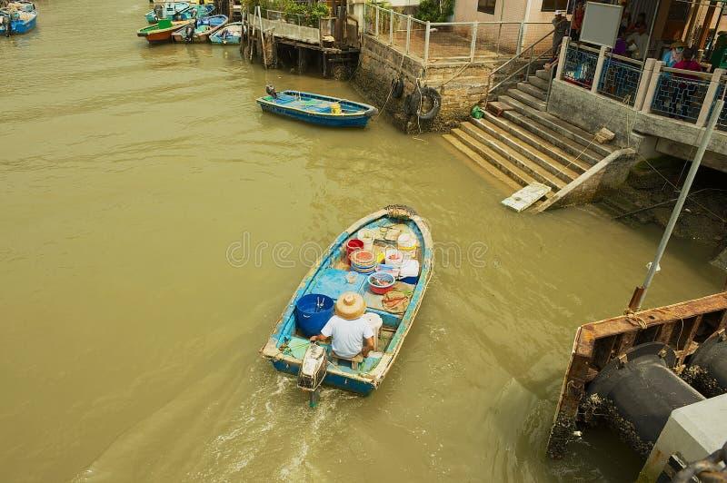 De lokale visser berijdt een oude boot bij het Tai O vissersdorp in Hong Kong, China stock afbeelding