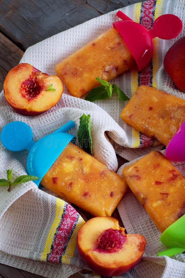 De lollies van het perzikijs op een keukenservet stock afbeelding