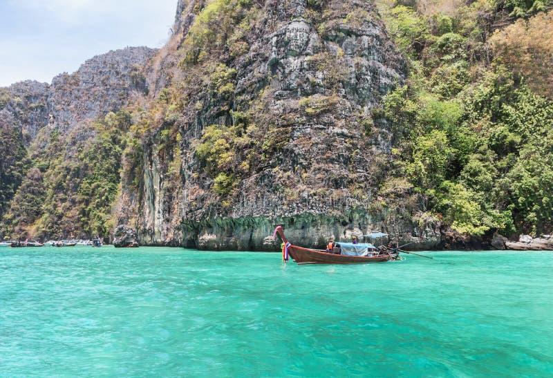 De Longtailboot het drijven bij Pileh-baai wordt vastgelegd is blauwe lagune met kalksteenrots bij phi phi eiland Krabi, Thailand royalty-vrije stock afbeeldingen