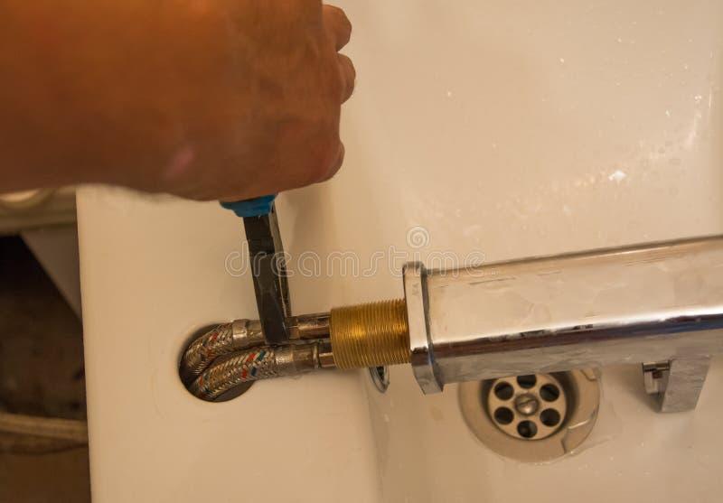 De loodgieter herstelt een lekke tapkraan in badkamers royalty-vrije stock fotografie
