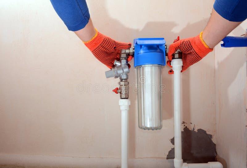 De loodgieter installeert een nieuwe waterfilter Filtersysteem voor waterbehandeling Installatie van een reductiemiddel en een wa royalty-vrije stock foto