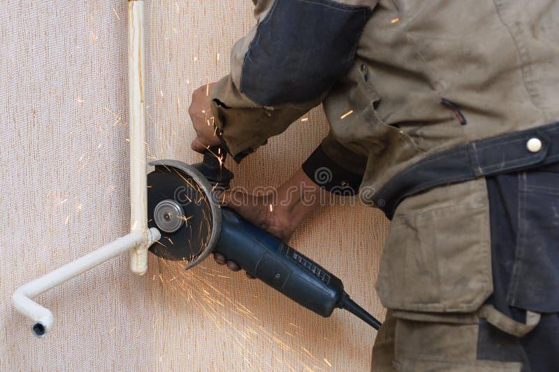 De loodgieter snijdt de metaalpijp met een hoekmolen royalty-vrije stock afbeelding