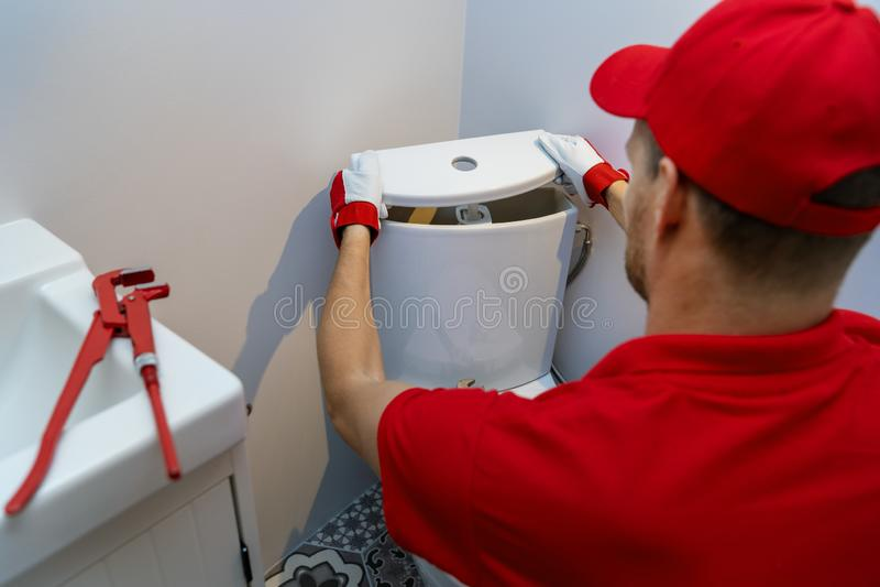 De loodgieterswerkdiensten - loodgieter die in badkamers werken die het watertank installeren van toiletwc royalty-vrije stock afbeelding