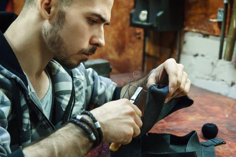 De looier naait leerpunt in workshop stock foto