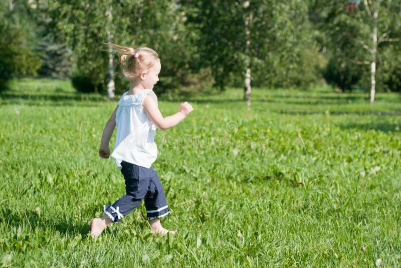 De looppas van het meisje rond het groene gras stock afbeeldingen