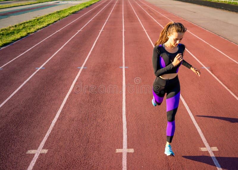 De looppas van de meisjesatleet op het stadion bij zonsondergang royalty-vrije stock foto