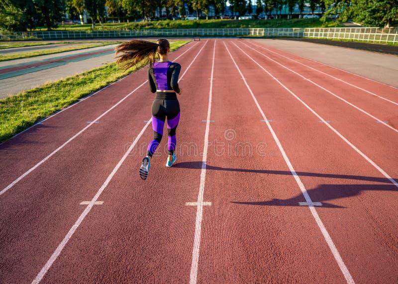 De looppas van de meisjesatleet op het stadion bij zonsondergang royalty-vrije stock afbeelding