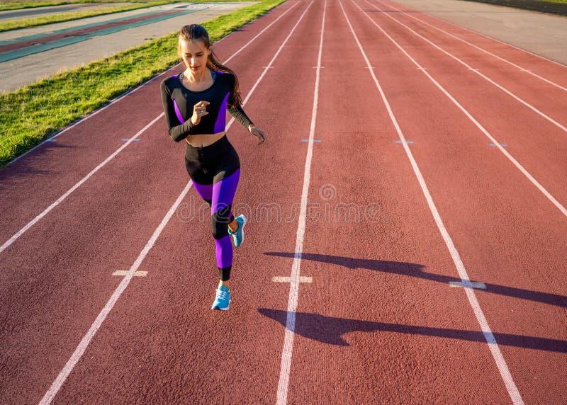 De looppas van de meisjesatleet op het stadion bij zonsondergang stock fotografie