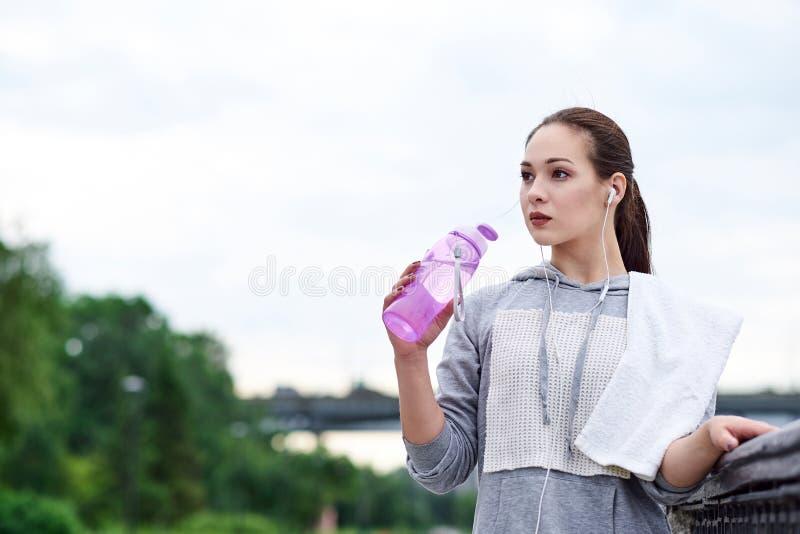 De lopende Aziatische vrouw heeft onderbreking, drinkwater tijdens looppas in de zomerpark stock afbeeldingen