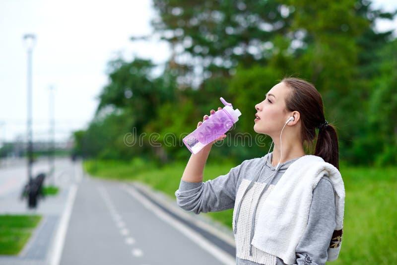 De lopende Aziatische vrouw heeft onderbreking, drinkwater tijdens looppas in de zomerpark royalty-vrije stock afbeelding