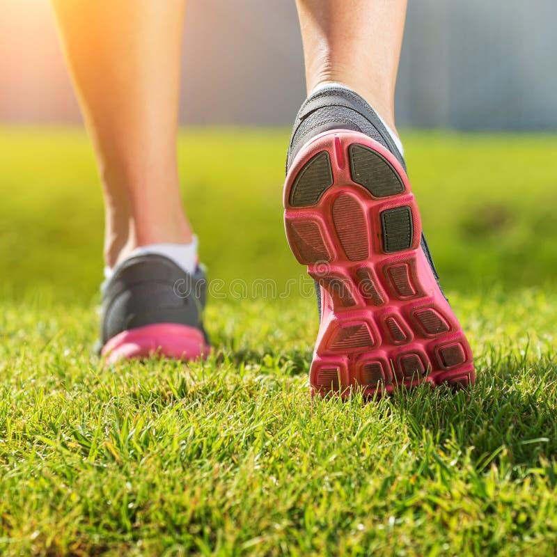 De lopende benen van vrouwen, het roze-grijze detail van de sportenschoen stock afbeelding