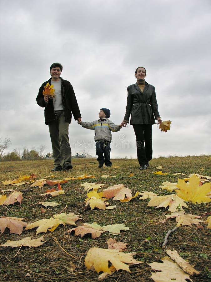 De lopende familie met de herfst gaat weg en betrekt stock afbeeldingen