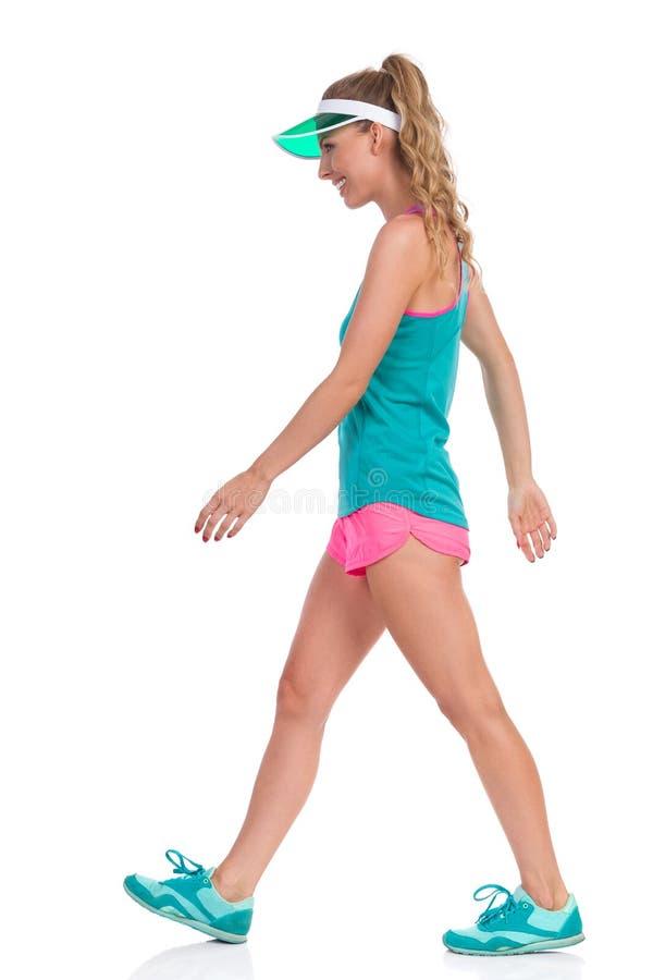 De lopende Glimlachende Vrouw in Sporten kleedt Geïsoleerd Zijaanzicht stock fotografie