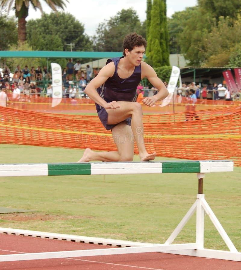 De lopende steeplechase van de atleet stock afbeeldingen