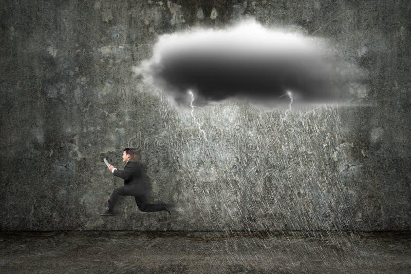 De lopende tablet van de zakenmanholding met donkere wolken die regenen en stock foto