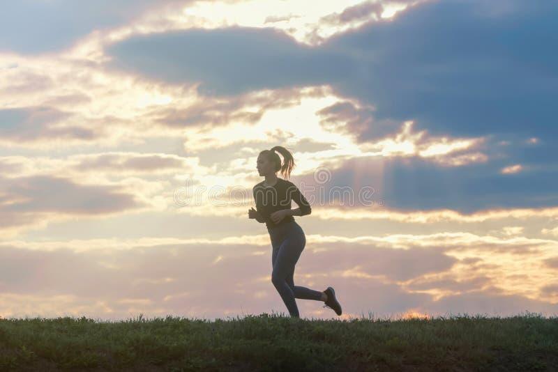De lopende training van de vrouwenochtend Vrouwelijke agent Het aanstoten tijdens zonsopgang Training in een Park Sportieve Jonge stock fotografie