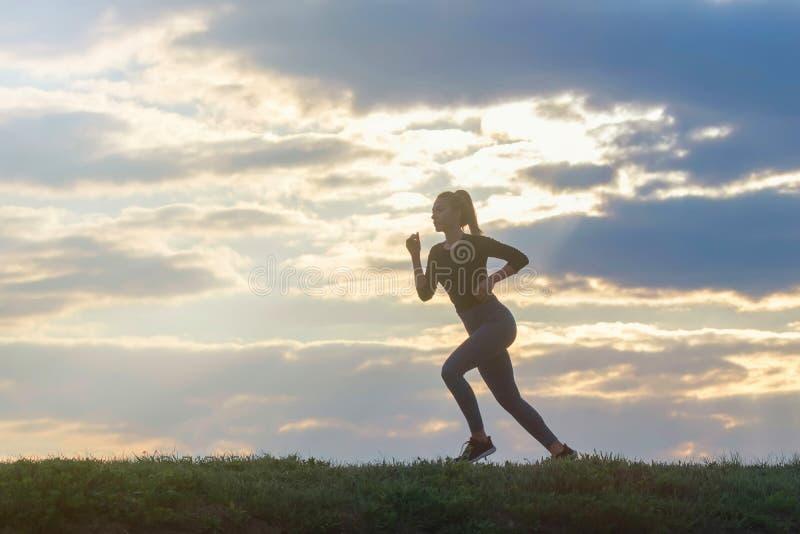 De lopende training van de vrouwenochtend Vrouwelijke agent Het aanstoten tijdens zonsopgang Training in een Park Sportieve Jonge royalty-vrije stock fotografie