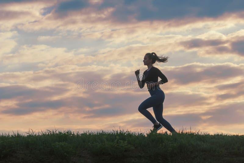 De lopende training van de vrouwenochtend Vrouwelijke agent Het aanstoten tijdens zonsopgang Training in een Park Sportieve Jonge royalty-vrije stock afbeelding