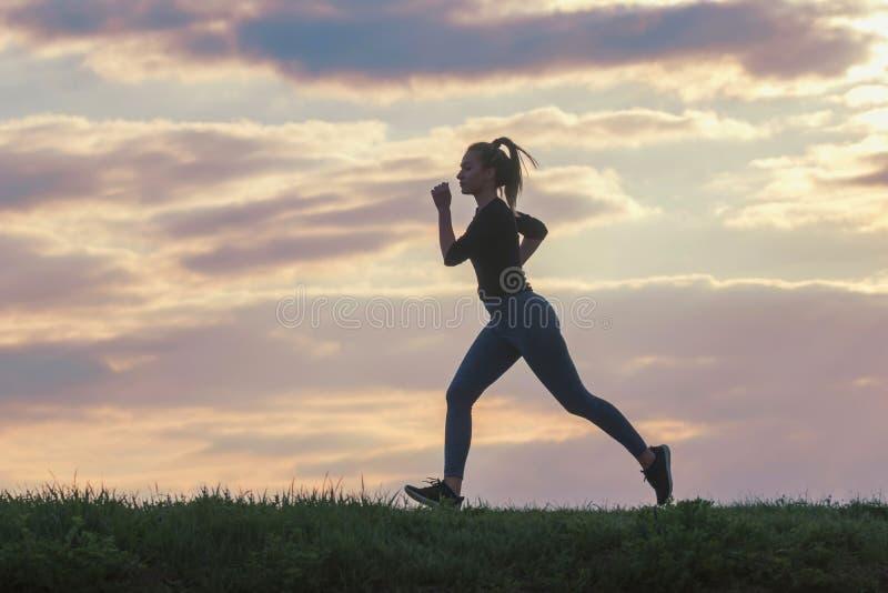 De lopende training van de vrouwenochtend Vrouwelijke agent Het aanstoten tijdens zonsopgang Training in een Park Sportieve Jonge royalty-vrije stock foto's