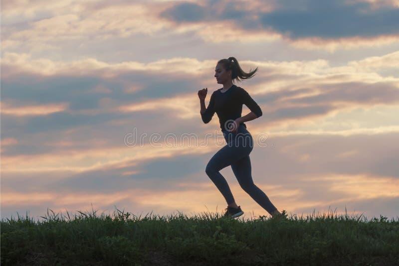 De lopende training van de vrouwenochtend Vrouwelijke agent Het aanstoten tijdens zonsopgang Training in een Park Sportieve Jonge royalty-vrije stock foto