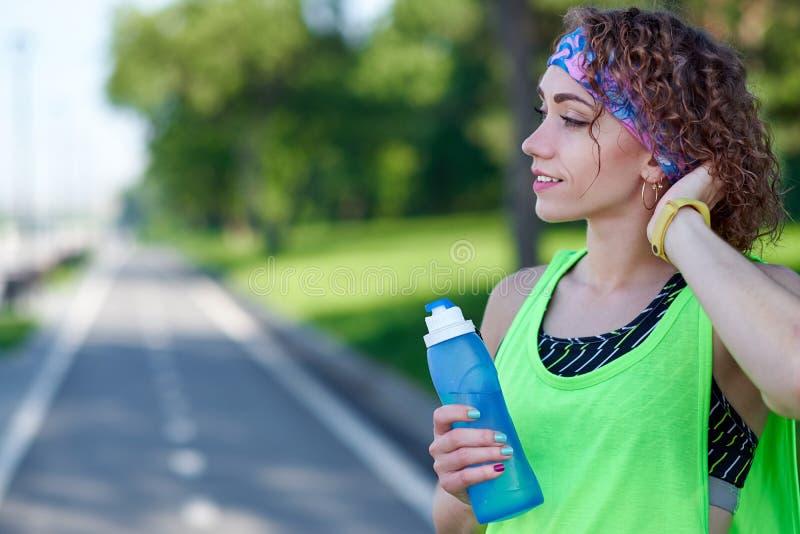 De lopende vrouw heeft onderbreking, drinkwater tijdens looppas in de zomerpark royalty-vrije stock fotografie