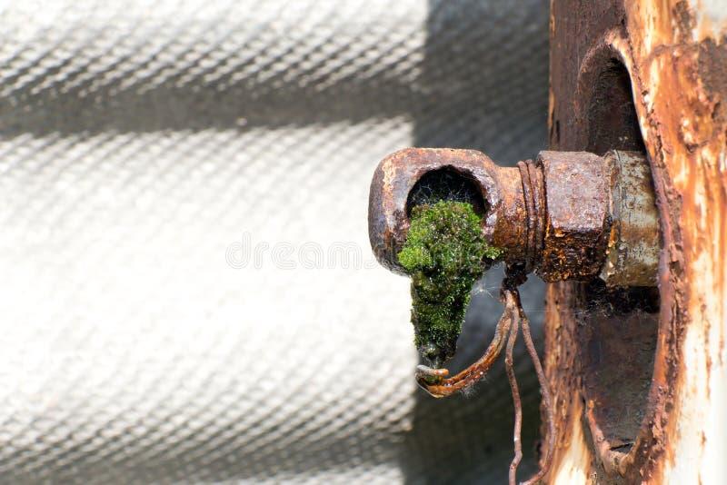 De los tubos oxidados viejos (grifo roto) está goteando el agua imagen de archivo