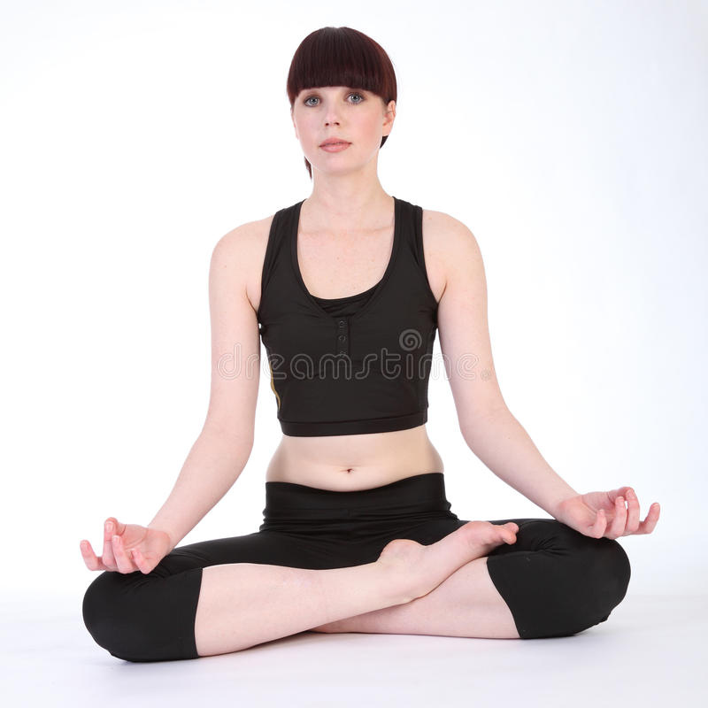 De lotusbloem van de yoga stelt padmasana door geschikte jonge vrouw stock fotografie