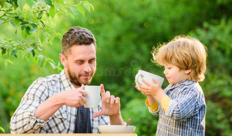 de ?lskar att ?ta tillsammans Den helgfrukostfadern och sonen äter utomhus- Litet pojkebarn med farsan sund mat familj arkivfoton