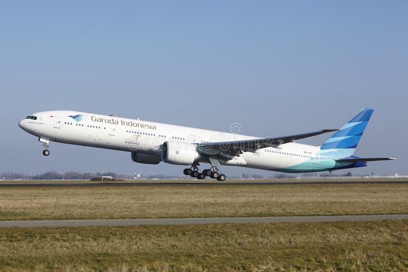 De Luchthaven Schiphol van Amsterdam - Garuda Indonesia Boeing 777 stijgt op stock fotografie