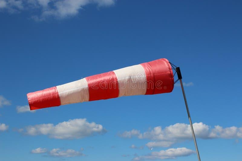 De luchthaven windsock op blauwe hemelachtergrond wijst op lokale ontzettende wind stock foto's
