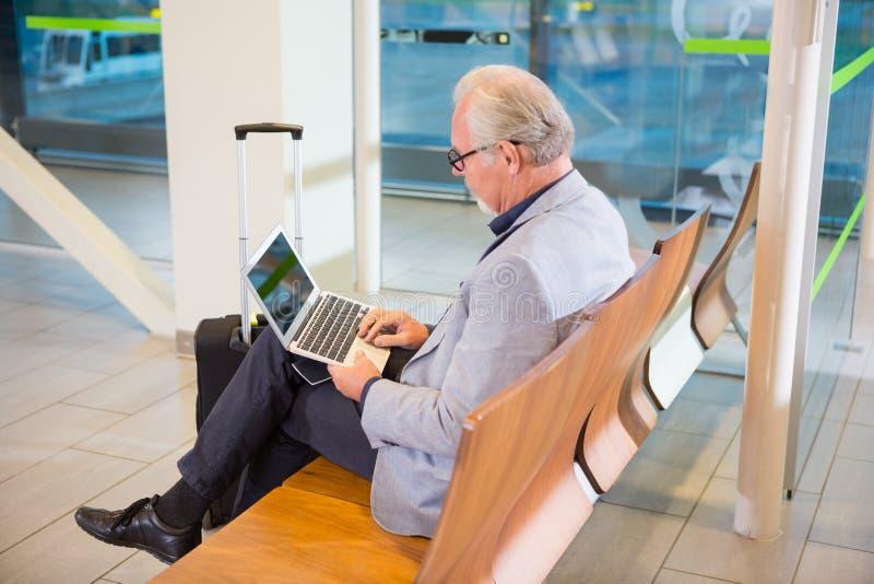 De Luchthaventerminal van zakenmanusing laptop at royalty-vrije stock fotografie