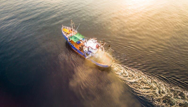 De luchthommelfoto van een vissersvaartuig die het is netten slepen Korfu Griekenland stock fotografie