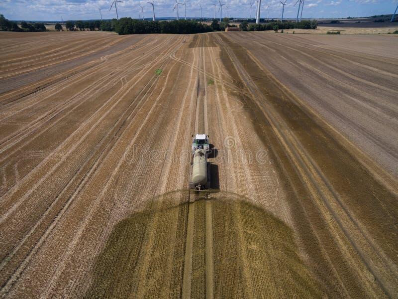 de luchtmening van een de landbouwtractor met een aanhangwagen bevrucht een vers geploegd agriculural gebied met mest royalty-vrije stock foto's
